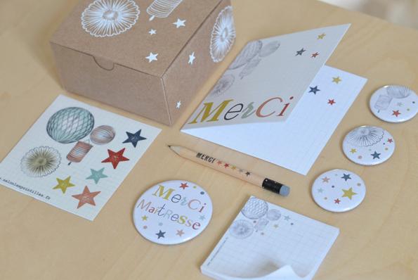 Une boite kraft (10x10x5 cm) sérigraphiée à la main accompagnée d'une carte double MERCI, de 3 aimants 38 mm (étoiles et lampions), 1 aimant 55 mm (MERCI MAITRESSE), 1 bloc de 50 notes autocollantes, 1 mini-planche de stickers (lampions et étoiles séparées) et 1 crayon de bois MERCI avec sa gomme. Prix : 19€.